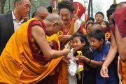 Его Святейшество Далай-лама приветствует детей по прибытию в Дорзонг Тубтен Донгак Рабгьял Чолинг для проведения церемонии освящения 12 сентября 2010. Фото: DIIR