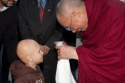 Его Святейшество Далай-лама подносит традиционный тибетский белый шарф маленькому пациенту больницы Крайстчерча, Новая Зеландия. 8 июня 2011 г. Фото: Cally Stockdale