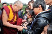 Местные жители показывают Его Святейшеству Далай-ламе фотографии близких, погибших во время разрушительного цунами в марте этого года. Исиномаки, Япония. 5 нояря 2011. Фото: Кимимаса Маяма