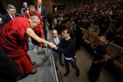 Его Святейшество Далай-лама приветствует своих почитателей после публичной лекции. Прага, Чехия. 11 декабря 2011.