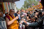 Его Святейшество Далай-лама приветствует толпу людей, встречающую его у тибетского монастыря в Бодхгае, Индия. 31 декабря 2011. Фото: Тензин Чойджор (офис ЕСДЛ)