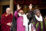 Его Святейшество Далай-лама, архиепископ Туту и его супруга Леа Туту приветствуют собравшихся по заврешении приветственной церемонии в главном тибетском храме. Дхарамсала, Индия. 10 февраля 2012. Фото: Тензин Чойджор (офис ЕСДЛ)