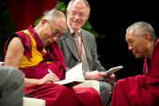 """Его Святейшество Далай-лама подписывает книги для своих слушателей во время встречи """"Мир и всеобщая ответственность"""". Зальцбург, Австрия. 21 мая 2012 г. Фото: Тензин Чойджор (Офис ЕСДЛ)"""