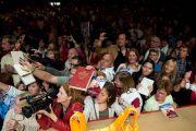 """Люди передают на сцену книги, чтобы получить автограф Его Святейшество Далай-ламы во время встречи """"Мир и всеобщая ответственность"""". Зальцбург, Австрия. 21 мая 2012 г. Фото: Тензин Чойджор (Офис ЕСДЛ)"""