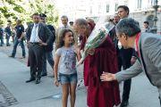 Девочка дарит цветы Его Святейшеству Далай-ламу по прибытии в мэрию Милана, Италия. 26 июня 2012 г. Фото: Тензин Чойджор (Офис ЕСДЛ)