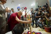 """Его Святейшество Далай-лама зажигает лампаду во время торжественного открытия новой больницы """"Фортис"""", построенной в Кангре неподалеку от Дхарамсалы, где находится резиденция Его Святейшества. Штат Химачал-Прадеш, Индия. 4 июля 2012 г. Фото: Тензин Чойджор (Офис ЕСДЛ)"""