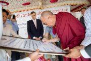 Его Святейшество Далай-лама ставит автограф на доске, на которой записано торжественное обязательство учеников тибетской школы Шринагара, штат Джамму и Кашмир, Индия, следовать примеру Далай-ламы и способствовать распространению общечеловеческих ценностей и межрелигиозной гармонии. 14 июля 2012 г. Фото: Тензин Чойджор (Офис ЕСДЛ)