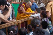 Его Святейшество Далай-лама шутливо здоровается с тибетским мальчиком по дороге в главный тибетский храм Цуглакан перед началом трехдневных учений. Дахарамсала, Индия. 4 сентября 2012 г. Фото: Abhishek Madhukar