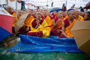 Монахи внимают учениям Его Святейшества Далай-ламы в парке Норлинг под проливным дождем. Тибетское поселение Декьилинг неподалеку от г. Дехрадун, Индия. 14 сентября 2012 г. Фото: Тензин Чойджор (Офис ЕСДЛ)
