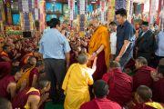 Его Святейшество Далай-лама проходит через толпу монахов, направляясь на  учения по 18 коренным текстам и комментариям традиции Ламрим в монастыре Дрепунг Лоселинг. 8 декабря 2012. Мандгод, Индия. Фото: Манюэль Бауэр
