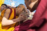Его Святейшество Далай-лама здоровается с монахом в монастыре Дрепунг Лоселинг, где проходили торжества по случаю 23-летия вручения Далай-ламе Нобелевской премии мира. Мандгод, Индия. 10 декабря 2012 г. Фото: Тензин Чойджор (офис ЕСДЛ)
