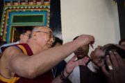 Его Святейшество Далай-лама закапывает девочке вакцину от полиомиелита в рамках индийского национального дня вакцинации в монастыре Дрепунг Лачи. Мандгод, Индия. 21 января 2013 г. Фото: Тезнин Чойджор (Офис ЕСДЛ)