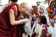 """Его Святейшество Далай-лама приветствует тибетскую девочку по прибытии в университет Тумкур для инаугурации международной конференции """"Страдания человечества в современном мире: мудрость Бхагавана Будды"""", организованной университетом Тумкур и монастырем Сера Чже. 6 марта 2013 г. Фото: Тензин Такла (офис ЕСДЛ)."""