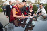 Его Святейшество Далай-лама подписывает фотографии по окончании посещения швейцарского парламента. Берн, Швейцария. 16 апреля 2013 г. Фото: Manuel Bauer