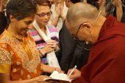 """Его Святейшество Далай-лама подписывает свою книгу для одной из слушательниц после лекции на стадионе """"Лэйкфрант Арена"""" в Новоорлеанском университете. Новый Орлеан, штат Луизиана, США. 18 мая 2013 г. Фото: Джереми Рассел (офис ЕСДЛ)"""
