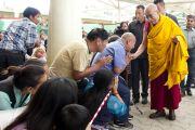 Его Святейшество Далай-лама приветствует своих последователей по пути в главный тибетский храм Дхарамсалы перед началом первого дня учений, которые он дарует по просьбе группы буддистов из Индии. Дхарамсала, штат Химачал-Прадеш, Индия. 1 июня 2013 г. Фото: Абхишек Мадхукар