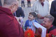 Его Святейшество Далай-лама беседует с незрячим мальчиком по дороге к месту проведения лекции «Культура сострадания». Рига, Латвия. 9 сентября 2013 г. Фото: Джереми Рассел (Офис ЕСДЛ)