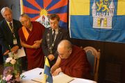 Его Святейшество Далай-лама с мэром Вунсторфа Рольфом-Акселем Эберхардтом (слева) оставляет запись в гостевой книге в Вунстрофской ратуше в Вунсторфе, Германия, 19 сентября 2013 г. Фото: Джереми Рассел (Офис ЕСДЛ)