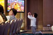 Второй день учений Его Святейшества Далай-ламы для буддистов из Монголии. Слушательница фотографирует экран, на который транслируется изображение для тех, кто сидит далеко от сцены. Дели, Индия. 3 декабря 2013 г. Фото: Тензин Чойджор (офис ЕСДЛ)
