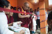Его Святейшество Далай-лама перерезает ленточку на открытии выставки работ учеников школы Центральной администрации тибетских школ (CTSA) в тибетском поселении в Бандаре. Штат Махараштра, Индия. 11 января 2014 г. Фото: Тензин Чойджор (офис ЕСДЛ)