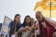 Его Святейшество Далай-лама по традиции зажигает светильник перед началом своего выступления на стадионе им. Неру. Гувахати, штат Ассам, Индия. 2 февраля 2014 г. Фото: Тензин Чойджор (офис ЕСДЛ)
