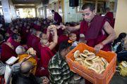 В начале учений Его Святейшества Далай-ламы в главном тибетском храме монахи раздают собравшимся хлеб. Дхарамсала, Индия. 31 марта 2014 г. Фото: Лобсанг Церинг (офис ЕСДЛ)