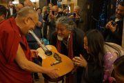 Тибетский певец Лотен Намлинг просит Его Святейшество Далай-ламу благословить его гитару. Осло, Норвегия. 7 мая 2014 г. Фото: Дежерми Рассел (офис ЕСДЛ)