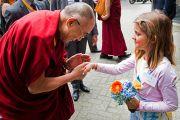 Его Святейшество Далай-лама здоровается с девочкой у входа в университет Эразма Роттердамского. Роттердам, Голландия. 12 мая 2014 г. Фото: Jurjen Donkers