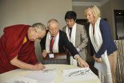 Его Святейшество Далай-лама ставит автограф на листе с тибетской каллиграфией работы Церинга Пхунцока из Тибетского дома в Германии. Франкфурт, Германия. 16 мая 2014 г. Фото: Manuel Bauer