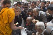 Его Святейшество Далай-лама подносит пожилому тибетцу хадак и пилюли в поселении Ней. Ладак, штат Джамму и Кашмир, Индия. 30 июня 2014 г. Фото: Тензин Чойджор (офис ЕСДЛ)