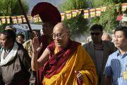 Его Святейшество Далай-лама машет рукой людям, встречающим его, в начале завершающей сессии предварительных учений перед посвящением Калачакры. Лех, Ладак, штат Джамму и Кашмир, Индия. 8 июля 2014 г. Фото: Манэуль Бауэр.