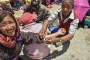 Участникам 33-го посвящения Калачакры раздали защитные шнурки. Лех, Ладак, штат Джамму и Кашмир, Индия. 10 июля 2014 г. Фото: Мануэль Бауэр.