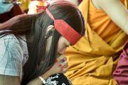 Участница учений с ритуальной повязкой на голове слушает наставления Его Святейшества Далай-ламы о вхождении в мандалу Калачакры. Лех, Ладак, штат Джамму и Кашмир, Индия. 11 июля 2014 г. Фото: Мануэль Бауэр.