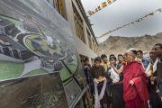 """Его Святейшество Далай-лама рассматривает план экодеревни """"Лотос"""" Буддийской ассоциации Ладака во время посещения общежития для бедных и обездоленных детей """"Сабу Тханг"""" в Чогламсаре неподалеку от Леха. Ладак, штат Джамму и Кашмир, Индия. 16 июля 2014 г. Фото: Тензин Чойджор (офис ЕСДЛ)."""