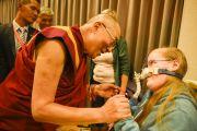 Его Святейшество Далай-лама здоровается с одной из слушательниц в инвалидном кресле перед началом послеполуденной лекции в гамбургском конгресс-холле. Гамбург, Германия. 23 августа 2014 г. Фото: Мануэль Бауэр