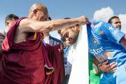 Его Святейшество Далай-лама вручает традиционный белый хадак игроку индийской крикетной сборной перед началом матча с командой Вест-Индии на стадионе Ассоциации крикета штата Химачал-Прадеш. Дхарамсала, Индия. 17 октября 2014 г. Фото: Тензин Чойджор (офис ЕСДЛ)