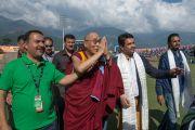 Его Святейшество Далай-лама машет рукой толпе болельщиков, покидая стадион Ассоциации крикета штата Химачал-Прадеш после матча между сборными Индии и Вест-Индии. Дхарамсала, Индия. 17 октября 2014 г. Фото: Тензин Чойджор (офис ЕСДЛ)