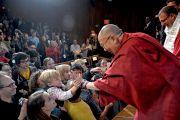 """Его Святейшество Далай-лама пожимает руки людям в зале перед началом форума """"Изменить мир к лучшему"""", организованного Центром за этику и ценности, ведущие к трансформации, действующий под эгидой Далай-ламы. Кембридж, штат Массачусетс, США. 31 октября 2014 г. Фото: Штат Массачусетс, США. 31 октября 2014 г. Фото: Сонам Зоксанг"""