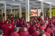 Некоторые из многих тысяч монахов, собравшихся на учения Его Святейшества Далай-ламы в монастыре Ганден Джангце, смотрят прямую трансляцию на большом экране в одном из залов храма. Мундгод, Индия. 24 декабря 2014 г. Фото: Тензин Чойджор (офис ЕСДЛ)