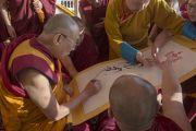 Его Святейшество Далай-лама подписывает торжественное заявление по случаю открытия нового общежития для монахов из Монголии, построенного в монастыре Дрепунг Гоманг. Мундгод, Индия. 25 декабря 2014 г. Фото: Тензин Чойджор (офис ЕСДЛ)