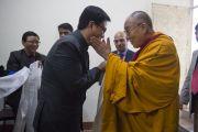 Его Святейшество Далай-лама приветствует министра внутренних дел Индии Кирена Риджиджу в монастыре Ганден Джангце перед началом церемонии, посвященной 55-летию со дня первых учений, дарованных Далай-ламой в Изгнании в Таванге. Мундгод, Индия. 26 декабря 2014 г. Фото: Тензин Чойджор (офис ЕСДЛ)