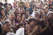Слушатели приветствуют Его Святейшество Далай-ламу в зале после обеденного перерыва в пятый день учений по 18 коренным текстам и комментариям традиции Ламрим. Мундгод, Индия. 27 декабря 2014 г. Фото: Тензин Чойджор (офис ЕСДЛ)