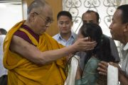 Его Святейшество Далай-лама благословляет свою последовательницу во время обеденного перерыва в пятый день учений по 18 коренным текстам и комментариям традиции Ламрим. Мундгод, Индия. 27 декабря 2014 г. Фото: Тензин Чойджор (офис ЕСДЛ)