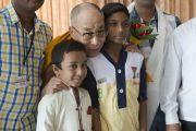 Его Святейшество Далай-лама фотографируется со своими юными поклонниками во время обеденного перерыва в пятый день учений по 18 коренным текстам и комментариям традиции Ламрим. Мундгод, Индия. 27 декабря 2014 г. Фото: Тензин Чойджор (офис ЕСДЛ)
