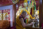 Его Святейшество Далай-лама зажигает масляный светильник во время посещения землячества Дхокханг монастыря Ганден. Мундгод. Индия. 28 декабря 2014 г. Фото: Тензин Чойджор (офис ЕСДЛ)
