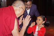 Его Святейшество Далай-лама здоровается со своей маленькой поклонницей в Пуне, штат Махараштра, Индия. 31 декабря 2014 г. Фото: Джереми Рассел (офис ЕСДЛ)