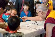 Его Святейшество Далай-лама угощает конфетами детей на встрече с тибетцами, живущими в Дании и соседних странах. Копенгаген, Дания. 10 февраля 2015 г. Фото: Джереми Рассел (офис ЕСДЛ).