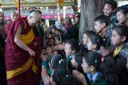 Его Святейшество Далай-лама приветствует тибетских школьников, покидая главный тибетский храм после учений по Джатакам. Дхарамсала, Индия. 5 марта 2015 г. Фото: Тензин Чойджор (офис ЕСДЛ)