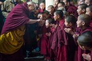 Его Святейшество Далай-лама шутливо приветствует маленьких монахов по дороге в главный тибетский храм, где он будет даровать учения по Джатакам. Дхарамсала, Индия. 5 марта 2015 г. Фото: Тензин Чойджор (офис ЕСДЛ)