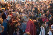 Его Святейшество Далай-лама идет к приготовленной для него ложе, по дороге здороваясь с тибетцами, собравшимися на открытие 20-го фестиваля тибетской оперы Шотон. Дхарамсала, Индия. 27 марта 2015 г. Фото: Тензин Чойджор (офис ЕСДЛ)